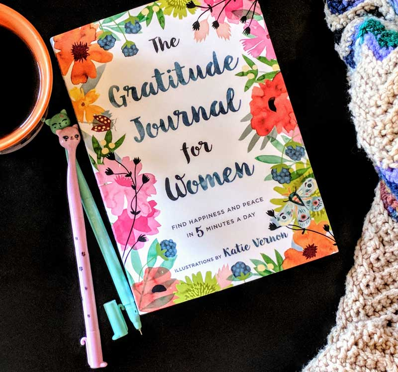 Gratitude Journal for women, a cup of coffee, my favorite crocheted blanket, and some kitty cat pins to write with.